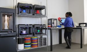 Classroom showing several 3D printers and filament on a rack