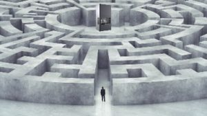 Man looking for a 3D printer at the center of a larger than life maze.