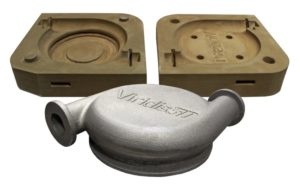 Two halves of a Viridis 3D printed sand casting mold for a pump housing and the finished gray metal part.